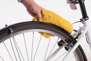 hand cleans a rear wheel of e commuter bike
