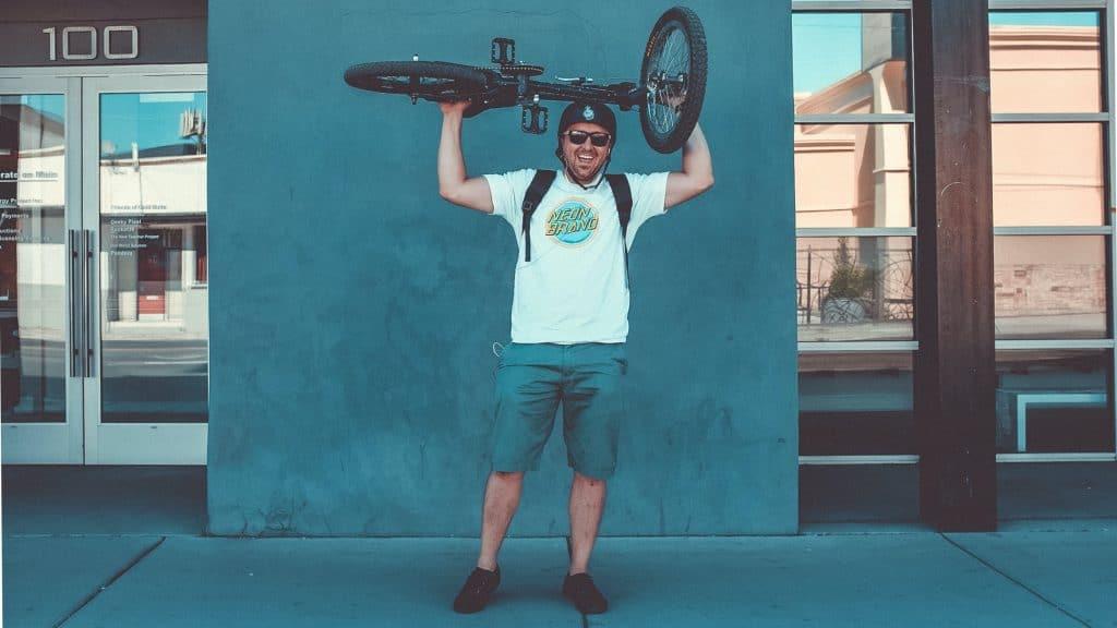 man lifts his bmx bike over head
