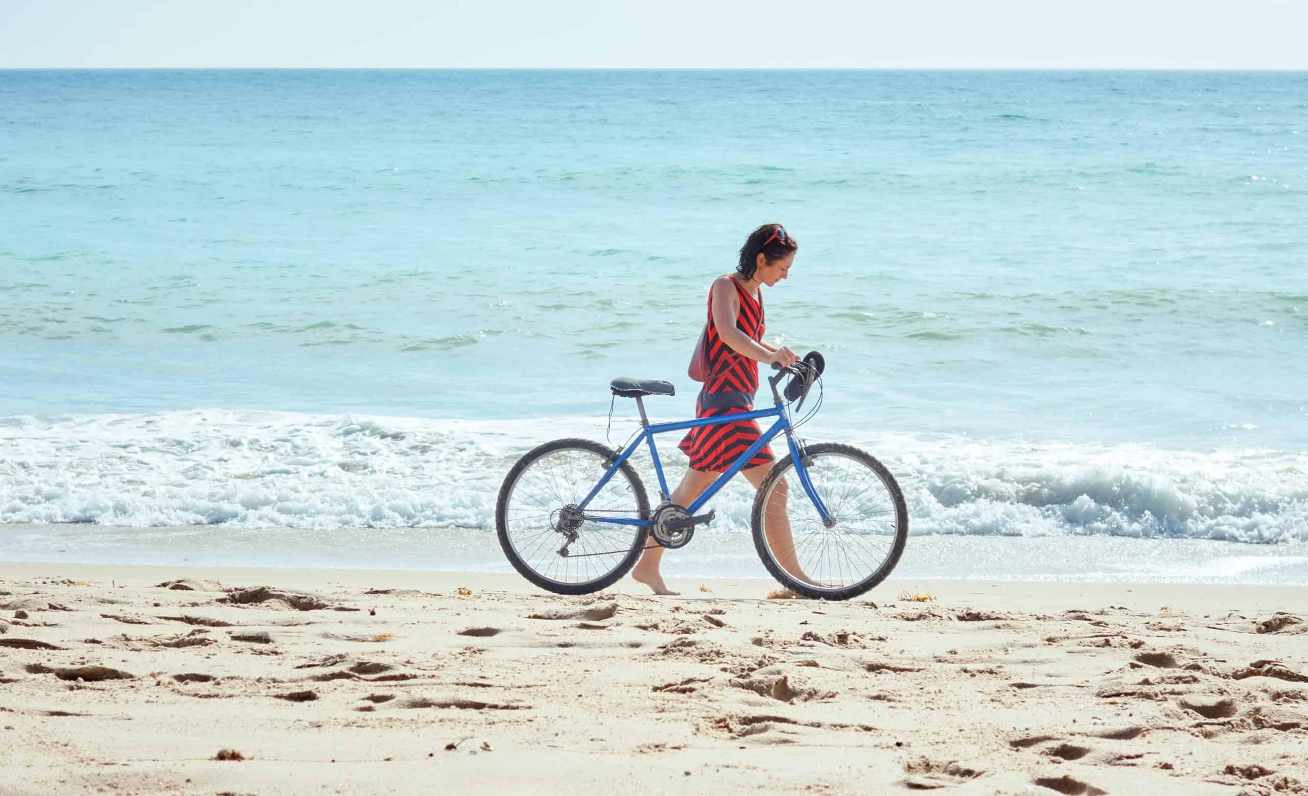 girl pushing bike on the beach
